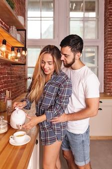 キッチンで朝食を取る若いカップル