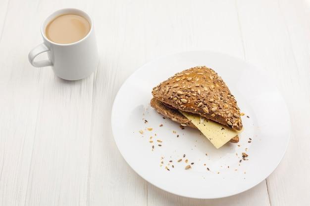 Тарелка с бутербродом и чашкой кофе