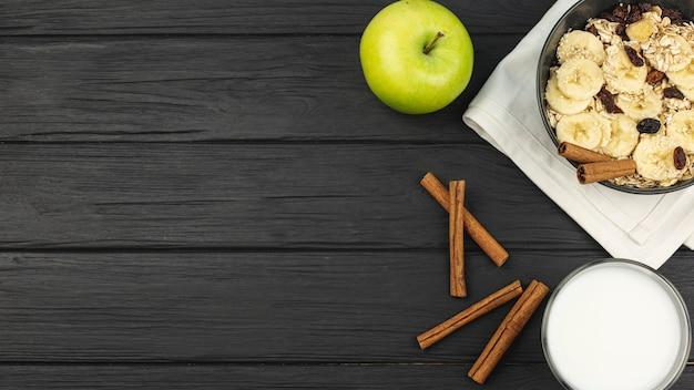 Яблоко и корица с миской овсянки с кусочками банана