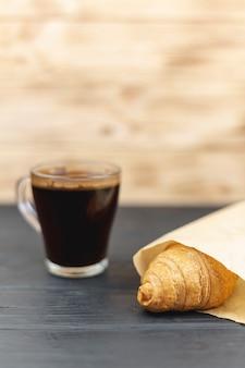 Кофейная чашка с круассаном на черном столе