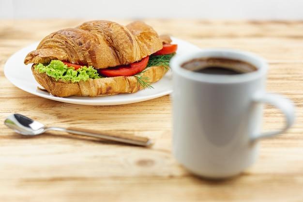 サンドイッチと木製のテーブルの上のコーヒーカップの白いプレート