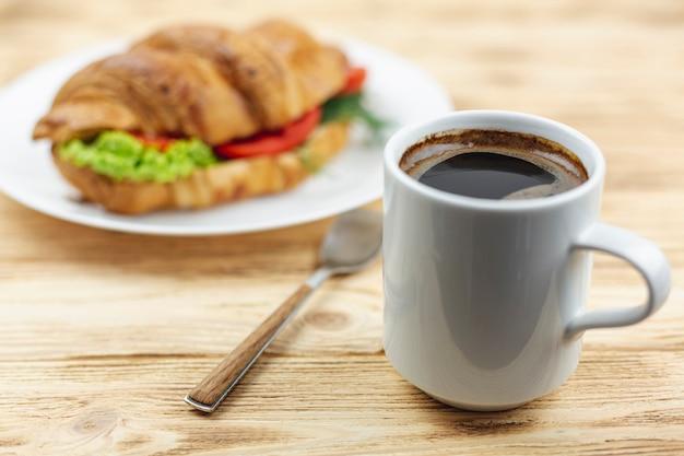 Кофейная чашка с бутербродом на белой тарелке