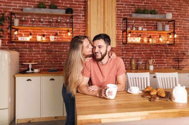 台所で朝食を取っているかわいいカップル