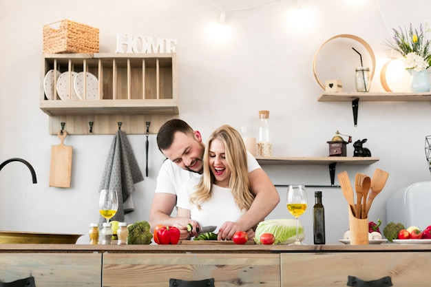 幸せな若いカップルが一緒に料理