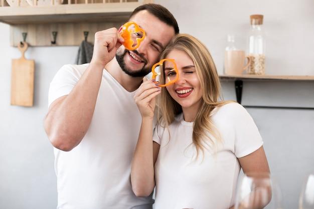 Счастливая пара играет с болгарским перцем