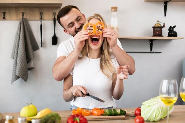 Радостная пара играет с болгарским перцем