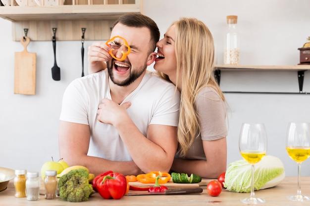 Смеющаяся пара играет с болгарским перцем