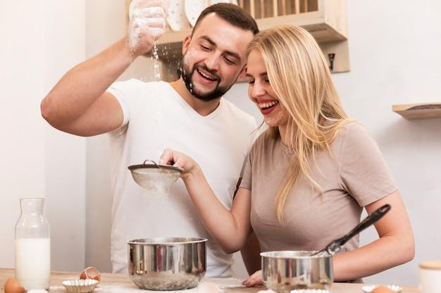 Мужчина и женщина наливают муку