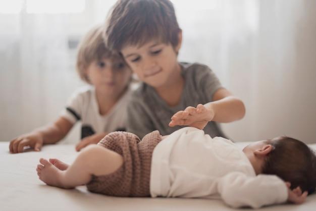 Дети смотрят на своего младшего брата
