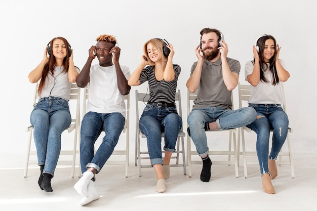 Друзья на стульях в наушниках слушают музыку