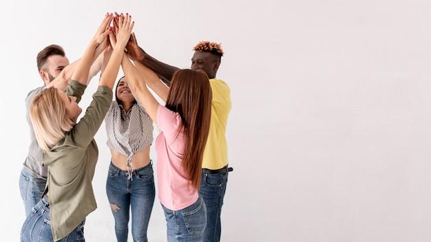 Вид сбоку друзей с поднятыми руками