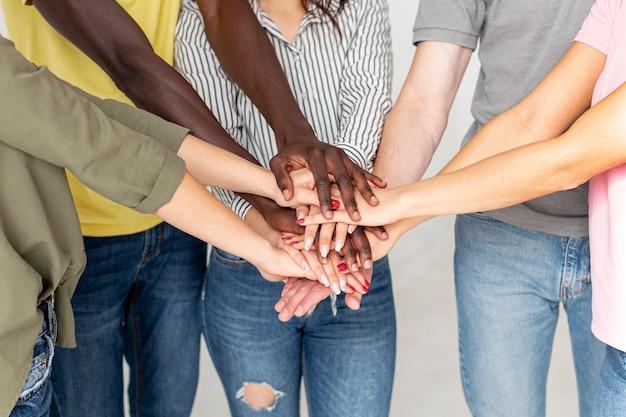 互いの上に手を持つ友人のグループ