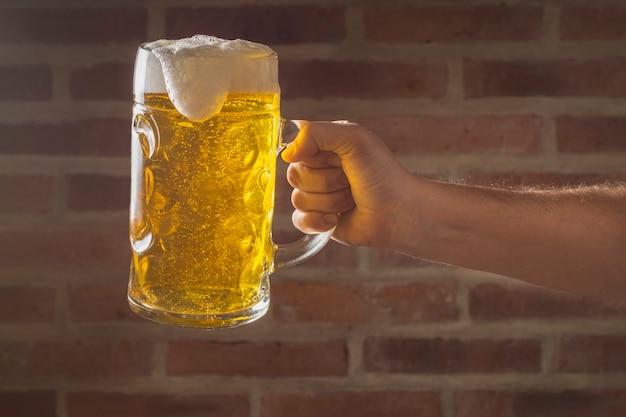 Вид спереди рука держит пинту с пивом