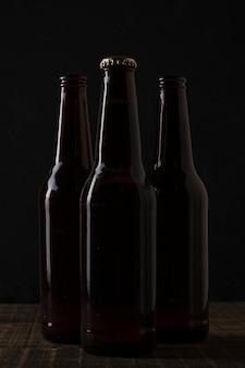 Вид спереди темных цветных бутылок пива