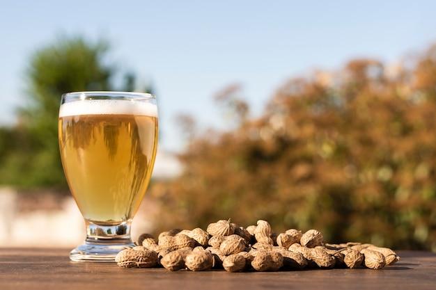 テーブルの上のピーナッツの横にビールとサイドビューガラス