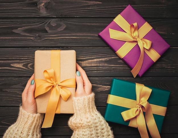 木製の背景にクリスマスプレゼントを両手