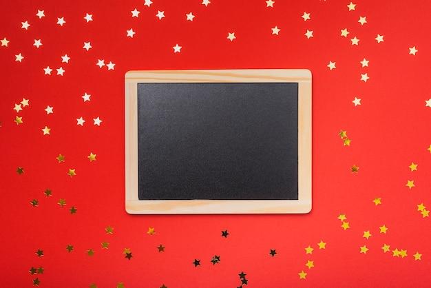 赤い背景と金色の星と黒板のモックアップ