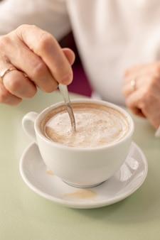 Высокий угол старших женщин, смешивая чашку кофе