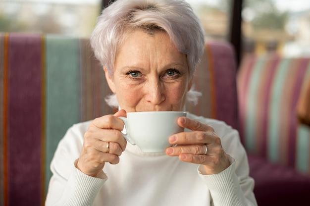 フロントビューのシニア女性がコーヒーを飲む