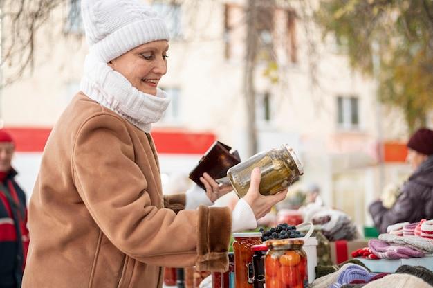 ピクルスの瓶をチェックするシニア女性