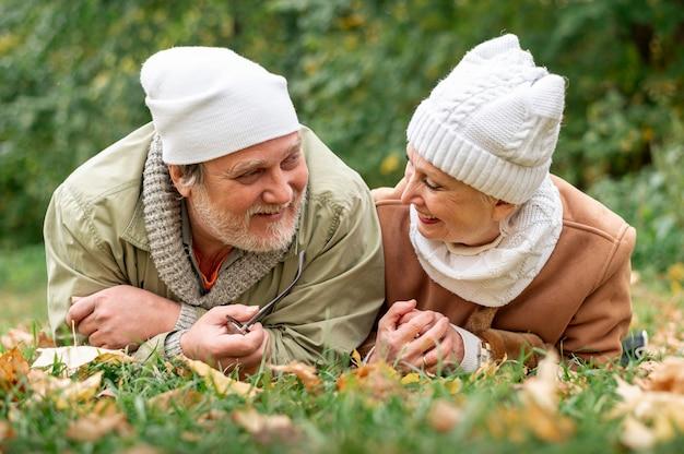 Низкий угол пожилые супружеские пары, сидя на поле с листьями