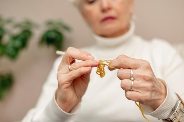 Крупный план старшего женского вязания дома