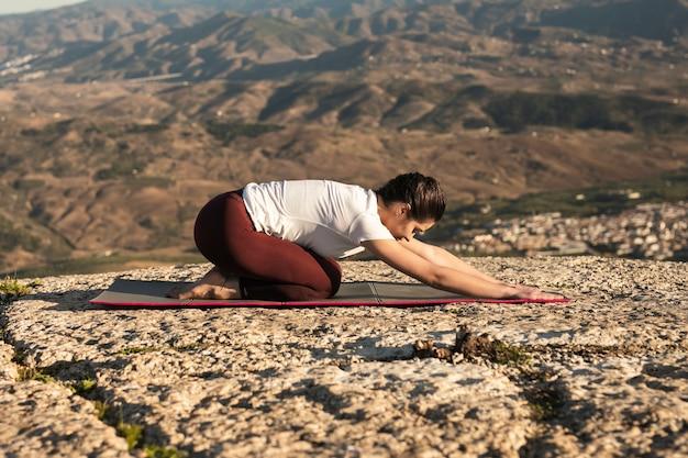 Женщина низкого угла на циновке практикуя йогу