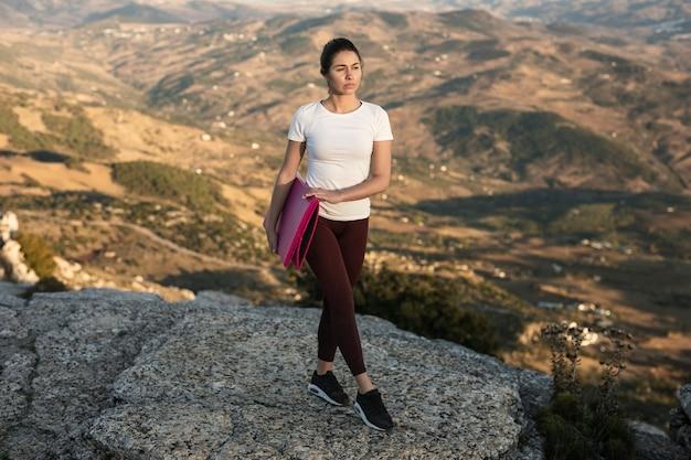 Женщина высокого угла на горе с циновкой йоги