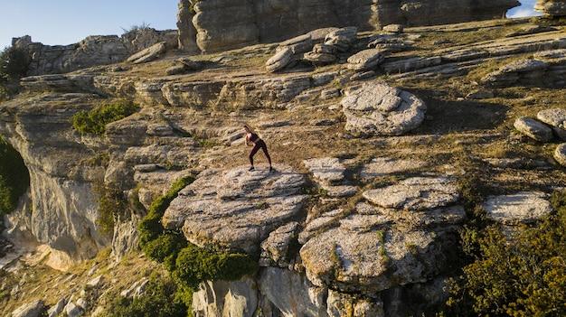 Молодая женщина практикующих йогу на природе