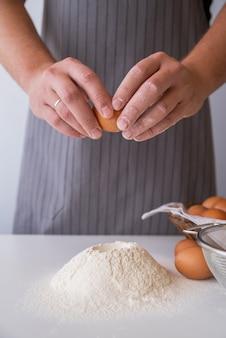 小麦粉で卵を割るシェフ