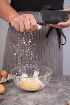 生地に小麦粉を振りかけるシェフ