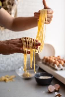 Шеф-повар держит свежеприготовленные макароны