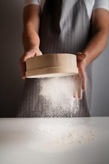 小麦粉をふるいにかけるシェフ