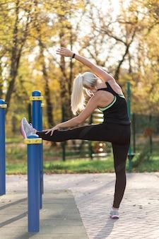 Вид сзади женщина делает упражнения на растяжку