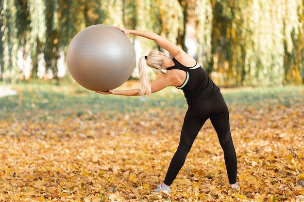Вид сзади красивая женщина с помощью гимнастического мяча