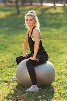 Женщина сидит на гимнастическом мяче и смотрит на фотографа