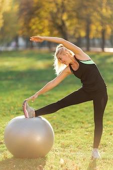 Блондинка растягивается с мячом для гимнастики