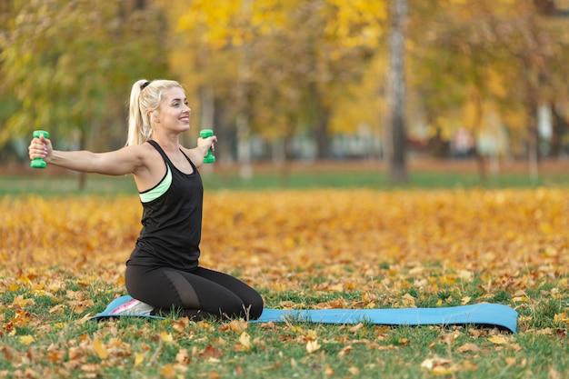 Блондинка занимается фитнесом на природе