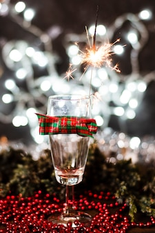 バックグラウンドでクリスマスライトとワイングラス
