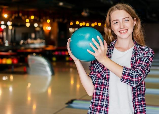 ボウリングのボールを保持している美しい若い女性