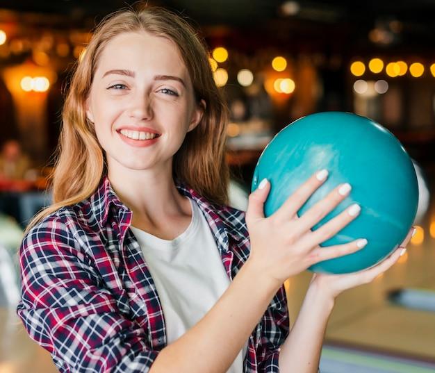 ボウリングのボールを保持している若い女性