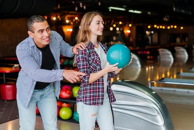 女と男がボウリングをプレイ