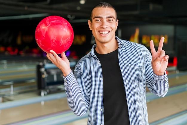 赤いボウリングのボールを保持している若い男