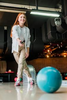 ボウリングのボールを投げる赤毛の女性