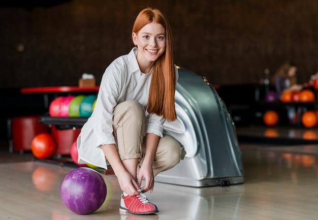 Счастливая женщина завязывает шнурки в боулинг-клубе