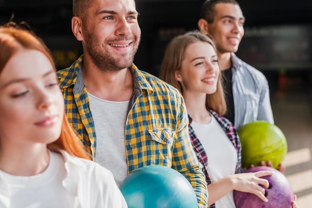 ボウリングのボールを保持している幸せな若いチーム
