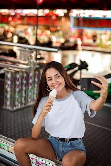 Женщина держит мороженое принимая селфи