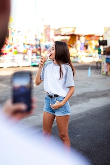 アイスクリームを食べているガールフレンドのボーイフレンド撮影写真