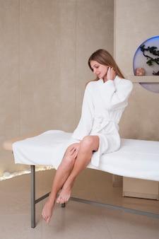Женщина в банный халат позирует на массажном столе в спа