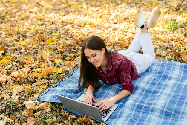 Молодая женщина, сидя на одеяле в парке
